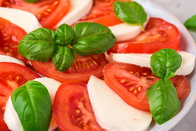 Włoska Sałatka Caprese Z Pokrojonymi Pomidorami, Mozzarellą, Bazylią, Oliwą Z Oliwek W Talerzu Premium Zdjęcia