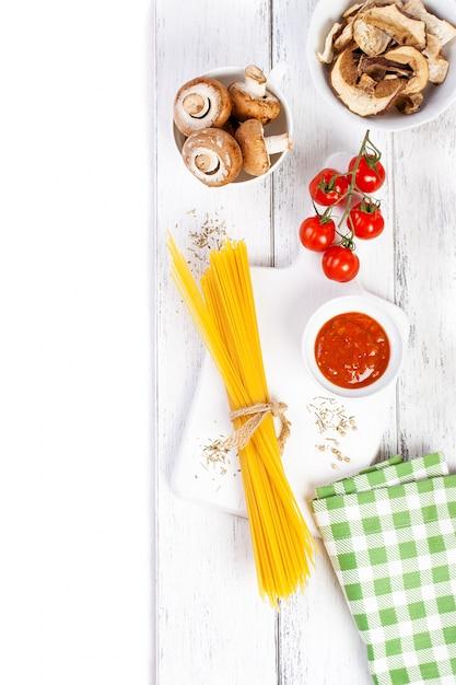 Włoski Spaghetti Champignon Suche Grzyby Sos Pomidorowy Wiśni świeżych Pomidorów I Przyprawy Na Drewnianym Tle Makaron Składników Widok Z Góry Kopi Pionowej Darmowe Zdjęcia