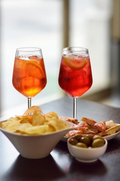 Włoskie aperitify / aperitif: kieliszek koktajlu (wino musujące z aperolem) i półmisek z przekąskami na stole. Premium Zdjęcia