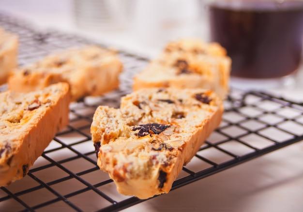 Włoskie Biscotti Na Stojaku Do Pieczenia I Szklanka Kawy Na Powierzchni Premium Zdjęcia