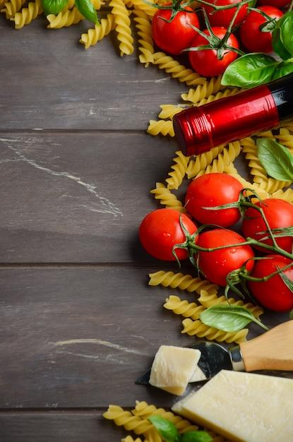 Włoskie jedzenie, surowe fusilli, pomidor, bazylia, ser i wino na drewnianym stole. Premium Zdjęcia