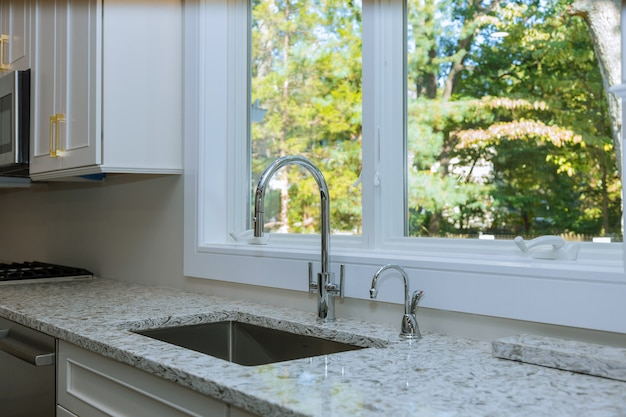 Wnętrze Nowoczesnej Kuchni Z Urządzeniami Na Blacie Kuchennym, Marmurowy Blat Z Białymi Szafkami Kuchennymi Premium Zdjęcia