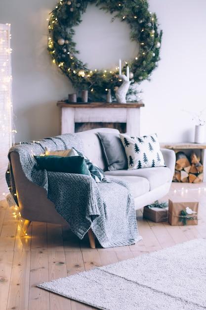 Wnętrze pokoju noworocznego z kominkiem, sofą i dużym wieńcem świątecznym nad kominkiem. Premium Zdjęcia