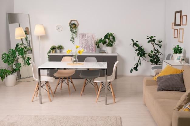 Wnętrze Przytulnego Salonu Ze Stołem Jadalnym, Kanapą Z Zielonymi Roślinami Doniczkowymi I Ramkami Na ścianach Premium Zdjęcia