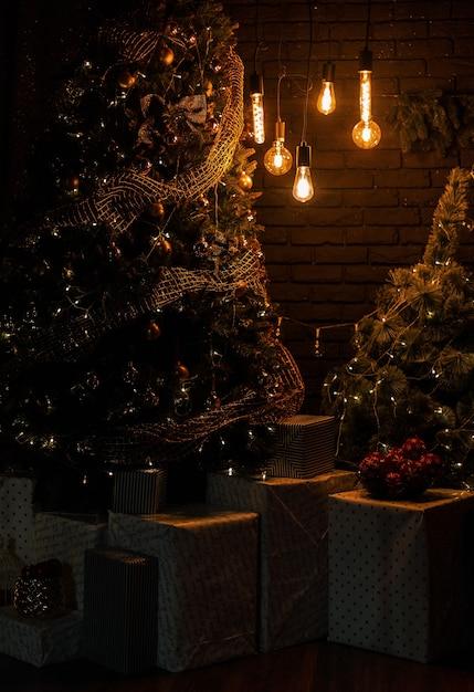 Wnętrze Salonu Z Jasnymi Lampami Vintage Z Choinką I Pudełkami Na Prezenty Wieczorem. Czekam Na Nowy Rok. Premium Zdjęcia
