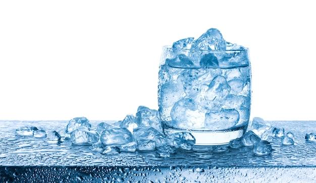 Woda z zdruzgotanymi kostkami lodu w szkle na białym tle Premium Zdjęcia
