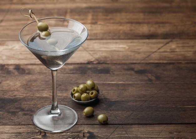 Wódka Martini Gin Koktajl W Oryginalnym Szkle Z Oliwkami W Metalowej Misce I Bambusowymi Patyczkami Na Drewnianej Powierzchni. Miejsce Na Tekst Premium Zdjęcia