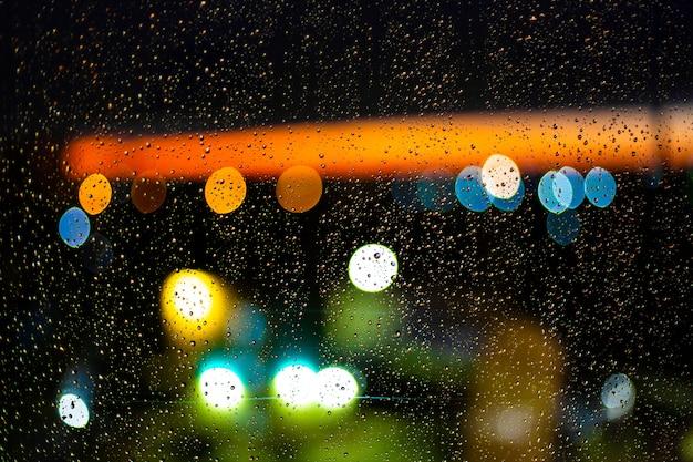 Wodna kropla przy okno i bokeh miasto w zmierzchu Premium Zdjęcia