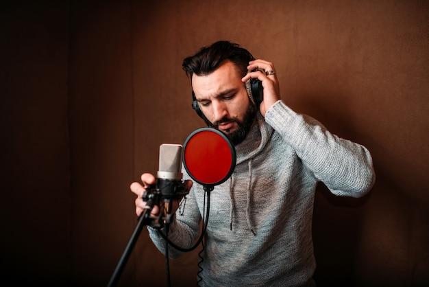 Wokalista Nagrywający Piosenkę W Studio Muzycznym. Wokalista W Słuchawkach Przeciwko Mikrofonowi. Premium Zdjęcia
