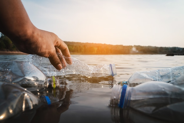 Wolontariusz zbiera plastikową butelkę w rzece, chroni środowisko przed koncepcją zanieczyszczenia. Premium Zdjęcia