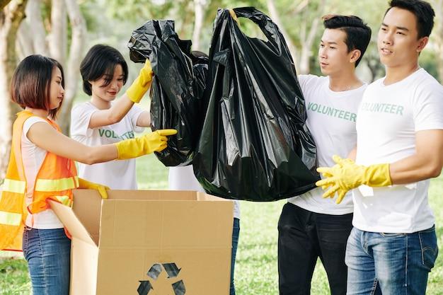 Wolontariusze Wkładają Worki Na śmieci Do Skrzynek Premium Zdjęcia