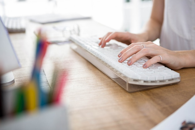 Womans ręce pisania na klawiaturze w biurze Premium Zdjęcia