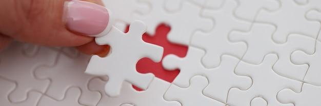 Womans Ręcznie Umieszcza Ostatni Kawałek Układanki Na Stole Zbliżenie. Rozwiązywanie Problemu Biznesowego Premium Zdjęcia