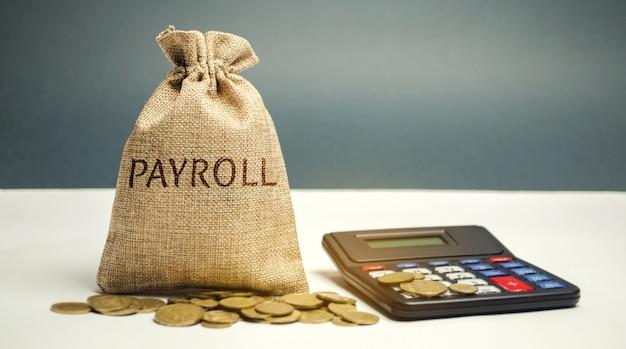 Worek pieniędzy ze słowem lista płac i kalkulator. Premium Zdjęcia