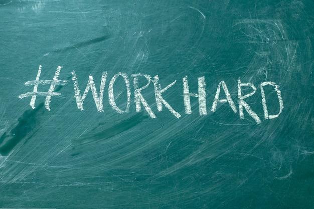 Workhard hashtag to ręcznie białą kredą na zielonej tablicy. Premium Zdjęcia