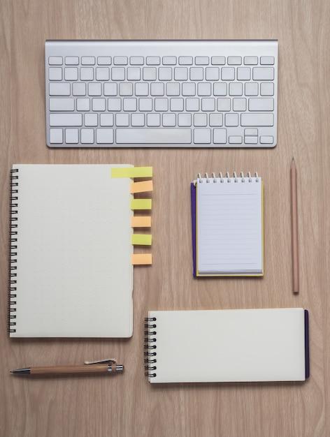 Workspace z notatnikami i klawiaturą na drewnianym tle Premium Zdjęcia