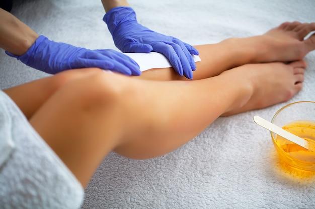 Woskowanie. Kosmetyczka Woskowanie Nogi Kobiety W Salonie Spa Premium Zdjęcia