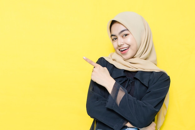 Wow I Zaskoczona Twarz Azjatyckiej Kobiety W Czarnych Ubraniach Z Ręką Wskazującą Na Pustą Przestrzeń. Premium Zdjęcia