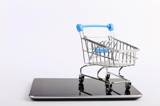 Wózek na zakupy stoi na smartfonie. koncepcja sprzedaży online. Premium Zdjęcia