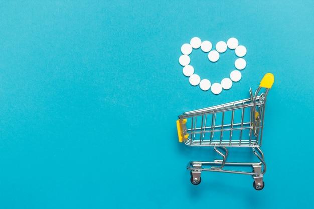 Wózek na zakupy wózek z bukietem różnych tabletek leku jeden niebieski tło. Premium Zdjęcia