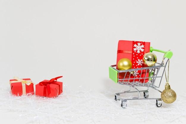 Wózek Na Zakupy Z Pudełka Na Prezenty I Złote Kule Na Płatku śniegu Na Białym Tle Darmowe Zdjęcia