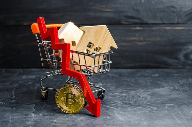 Wózek Supermarketowy Z Domami I Bitcoinem I Czerwoną Strzałką W Dół. Spadająca Wartość Premium Zdjęcia