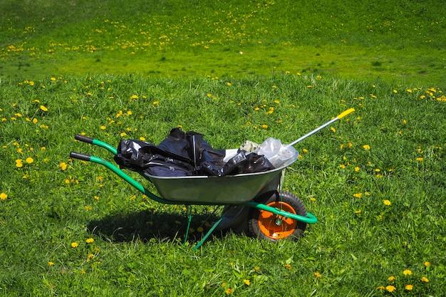 Wózek Ze śmieciami Na Zielonej Trawie. Czyszczenie Parku Po Grillowaniu W Przyrodzie. Premium Zdjęcia