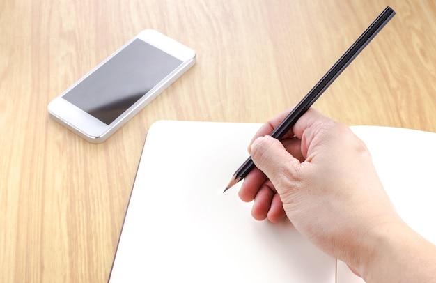 Wręcza Trzymać Czarnego Ołówek I Pisać Na Pustym Miejscu Otwiera Notatnika Z Smartphone Obok Go Na Drewnianym Stole Premium Zdjęcia