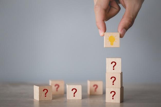 Wręcza Układać Drewnianego Bloku Sztaplowanie Z Ikona Znakiem Zapytania I Lampą Myśleć Z Znaka Zapytania Pojęciem ,. Premium Zdjęcia