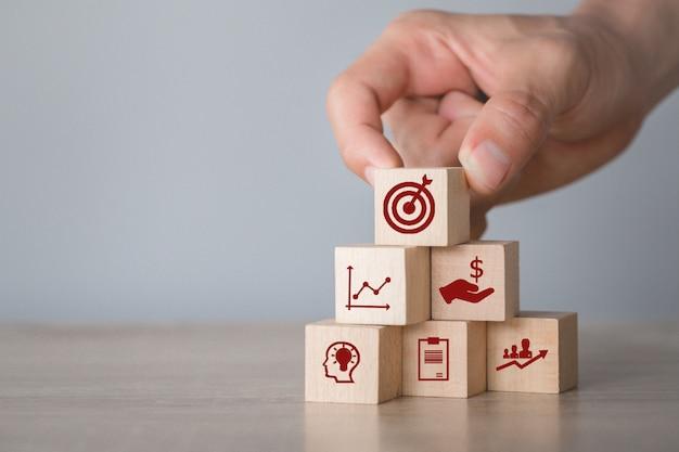 Wręcza Układać Drewnianego Bloku Sztaplowanie Z Ikony Strzała I Biznesem, Celując Biznesowego Pojęcie. Premium Zdjęcia