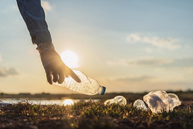 Wręcza Utrzymywać śmieciarską Butelkę Dla Czyścić Przy Parkiem W Ranku świetle. Koncepcja Eko Premium Zdjęcia