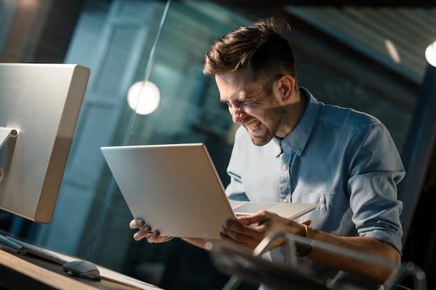 Wrzask Mężczyzna Z Zepsutym Laptopem Premium Zdjęcia