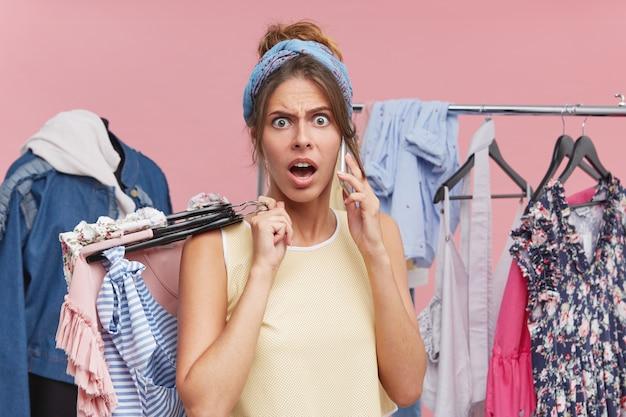 Wściekła Kobieta Kłócąca Się Przez Telefon, Stojąca W Przymierzalni Z Wieszakami Sukienek, Bluzek I Spódnic Przed Tępymi Ubraniami I Wieszakiem Z Ubraniami Darmowe Zdjęcia