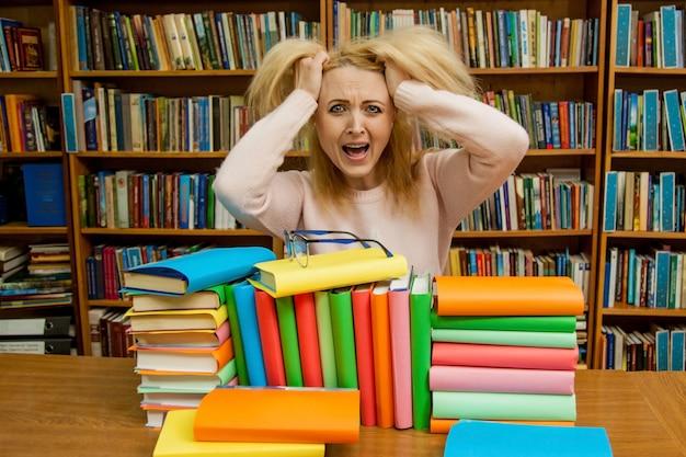 Wściekła kobieta krzyczy, kaukaska dziewczyna z długimi włosami, krzycząca z furią w bibliotece Premium Zdjęcia