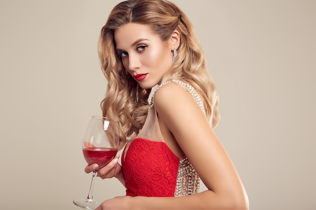 Wspaniała elegancka blondynki kobieta jest ubranym mody czerwoną suknię Premium Zdjęcia