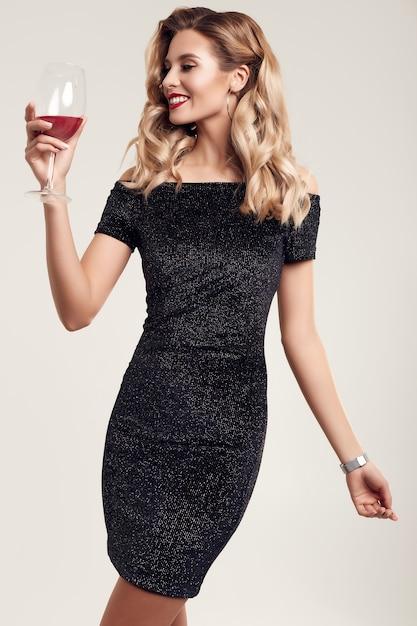 Wspaniała elegancka zmysłowa blondynki kobieta jest ubranym modną czarną suknię Premium Zdjęcia