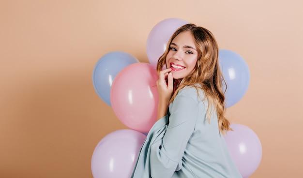Wspaniała Jasnowłosa Kobieta, Patrząc Przez Ramię Z Balonami W Błękitnym Stroju Darmowe Zdjęcia