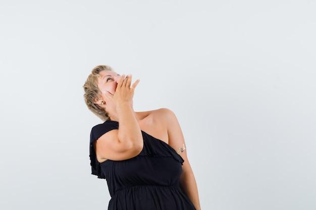 Wspaniała Kobieta śmiejąca Się, Patrząc W Czarną Bluzkę I Patrząc Wesoło. Przedni Widok. Miejsce Na Tekst Darmowe Zdjęcia