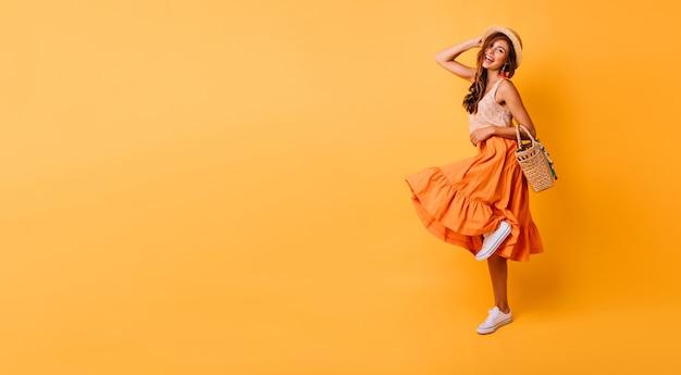 Wspaniała Kobieta W Długiej Spódnicy Jasny Taniec W Studio. Beztroska Inspirowana Modelka Z Przyjemnością Pozuje Na żółto. Darmowe Zdjęcia
