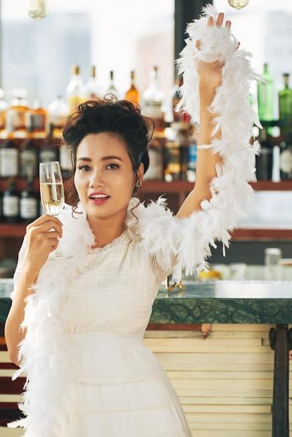 Wspaniała kobieta w fantazyjnej sukni i boa stojący z flet szampana w barze Darmowe Zdjęcia