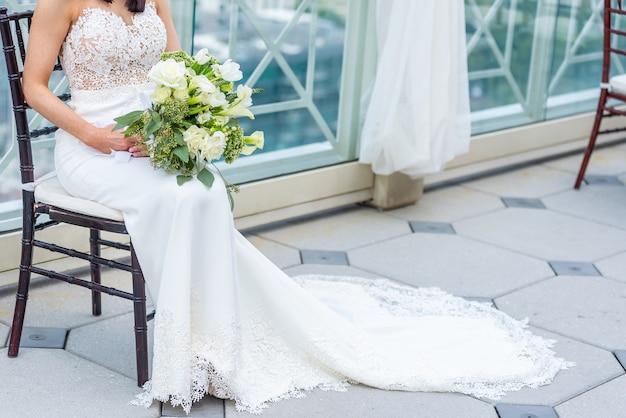 Wspaniała Panna Młoda W Luksusowej Sukni ślubnej Siedzi Na Krześle Z Bukietem ślubnym Darmowe Zdjęcia