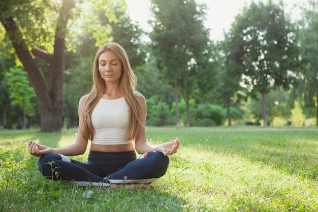 Wspaniała sportowa kobieta robi joga przy parkiem Premium Zdjęcia