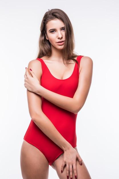 Wspaniały Model Dziewczyna W Czerwonym Apartamencie Pływackim Trzyma Ręce Na Nogach Na Białym Tle Darmowe Zdjęcia
