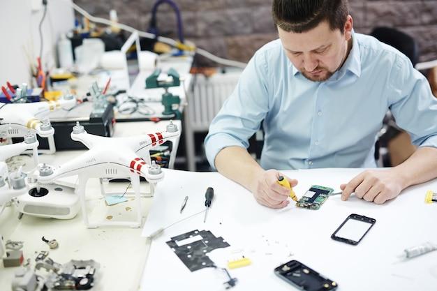 Współczesny Mężczyzna Pracujący W Sklepie Z Usługami Elektronicznymi Darmowe Zdjęcia