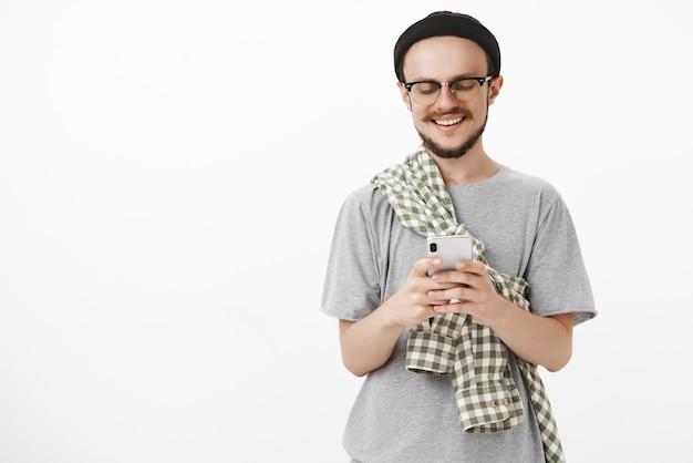 Współczesny Młody Chłopak Bawi Się Grając W Zabawną Aplikację W Smartfonie Darmowe Zdjęcia