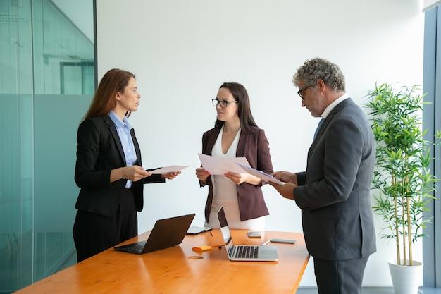 Współpracownicy, Którzy Odnieśli Sukces, Rozmawiają, Trzymają Dokumenty I Pracują Razem Darmowe Zdjęcia