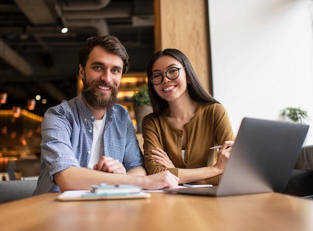Współpracownikami Siedzi Przy Stole W Biurze, Przy Użyciu Komputera Przenośnego, Pracując Razem Dla Projektu Uruchamiania. Sukces Koncepcji Biznesowej I Kariery. Portret Młodzi Szczęśliwi Deweloperzy Przy Miejscem Pracy Premium Zdjęcia