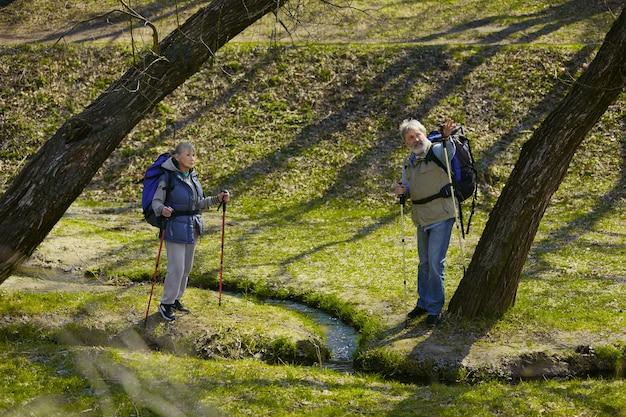 Wspomnienia Szczęścia. Starsza Rodzina Para Mężczyzny I Kobiety W Stroju Turystycznym Spaceru Na Zielonym Trawniku W Słoneczny Dzień W Pobliżu Potoku Darmowe Zdjęcia