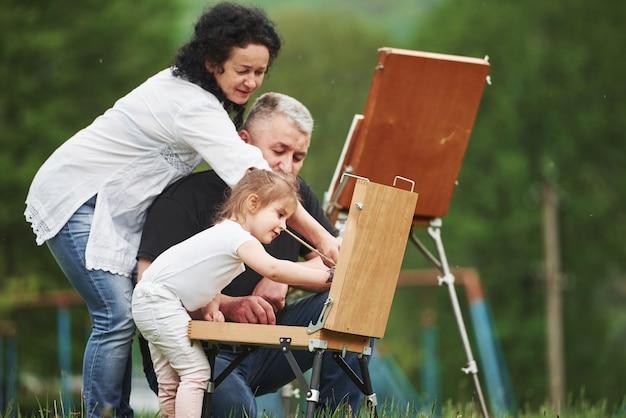 Wszyscy Są W Trakcie. Babcia I Dziadek Bawią Się Na świeżym Powietrzu Z Wnuczką. Koncepcja Malarstwa Darmowe Zdjęcia