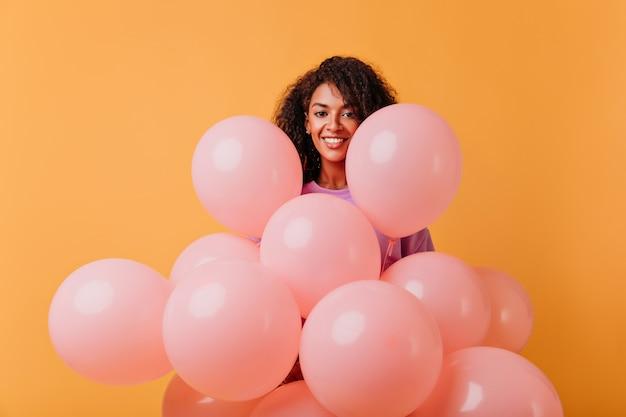 Wszystkiego Najlepszego Z Okazji Urodzin Dziewczyna Pozuje Z Wesołym Uśmiechem. Kryty Portret Całkiem Afrykańskiej Kobiety Z Balonów Na Pomarańczowo. Darmowe Zdjęcia